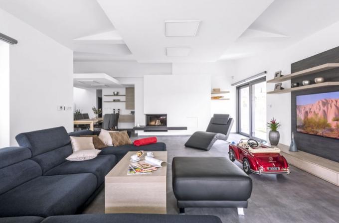 Velkou část přízemního prostoru zabírá modulární sedací souprava značky Phase s látkovým potahem, který se pěkně doplňuje s koženou podnožkou a lenoškou. Nábytek v obývacím pokoji je vyráběný na míru truhlářem podle návrhu architekta