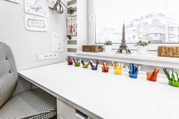 Barevné kelímky zapuštěné do desky pracovního stolu pomáhají dětem udržovat pořádek v pastelkách a fixách