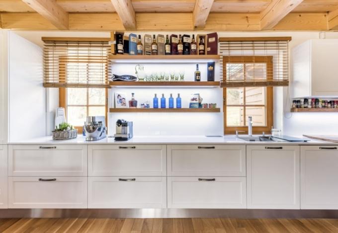 Lineární uspořádání kuchyňské linky získalo větší plasticitu díky dvířkům s rámečky a masivním dubovým policím s podsvícením LED pásky