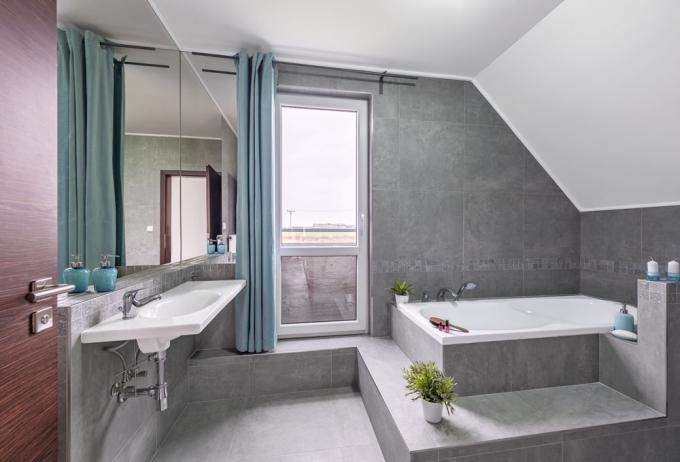 Koupelna působí díky velkorysému oknu prostorně a vzdušně. Zároveň jsme v ní ocenili vanu s obezdívkou, na níž si můžete pohodlně nalakovat nehty nebo popovídat si s partnerem naloženým v koupeli