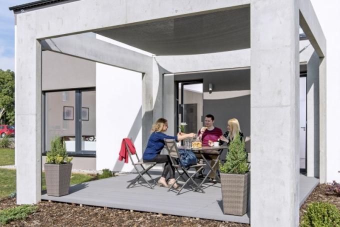 Zahrada s krytou terasou působí jako rozšířený obývací pokoj a navazuje tak plynule na společenskou část přízemí