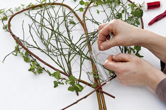 Kolem celého obvodusrdceobtočte břečťan a do drátků postupně zaplétejte připravené větvičky, nakonec upevněte vázičku/zkumavku na růži