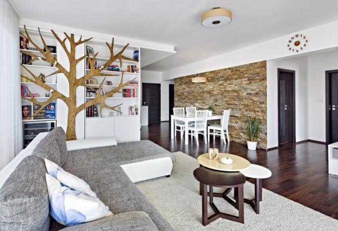Výrazným prvkem interiéru je strom, který designérka vytvořila přímo v truhlářské dílně, a obklad z přírodního kamene procházející přes celou hlavní obytnou část od jídelního koutu až ke stěně s televizí