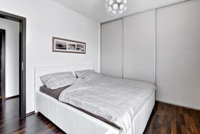 Tmavá podlaha prostupuje celým bytem a opticky tak spojuje jeho jednotlivé místnosti i všechny funkční zóny v harmonický celek