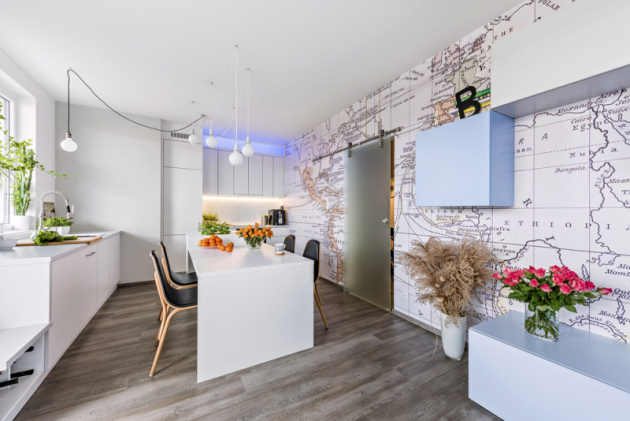 Jídelní stůl navazuje naostrůvek súložnými prostory. Doplňují ho černou kůží čalouněné židle Tram (Ton) adekorativní osvětlení sestavené zžárovek zavěšených našňůrách