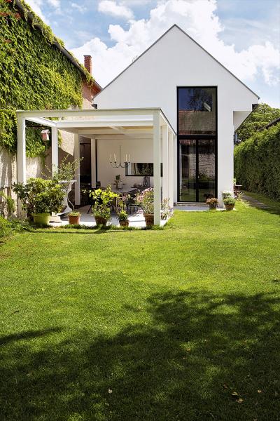 Pergola poskytuje další místo pro relaxaci avenkovní stolování. Díky velkému oknu má dům ztéto strany moderní tvář