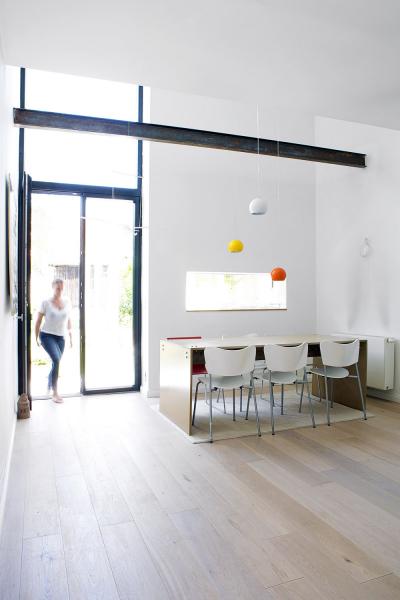 Dvoupodlažní okno tvoří plynulé propojení obytné části dozahrady. Se světlou výmalbou astřízlivým zařízením zajímavě kontrastují barevná svítidla