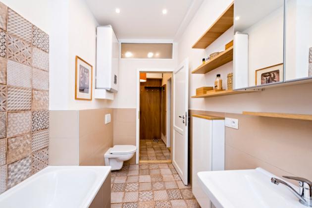 Koupelnu v průhledu propojuje s předsíní retro dlažba, která se efektně opakuje i ve výklenku za vanou. Místo pod obrázkem zaplní pračka