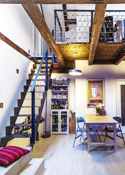 Ocelové schodnicové schodiště vede dovrchního patra nagalerii adopracovny sprosklenou podlahou