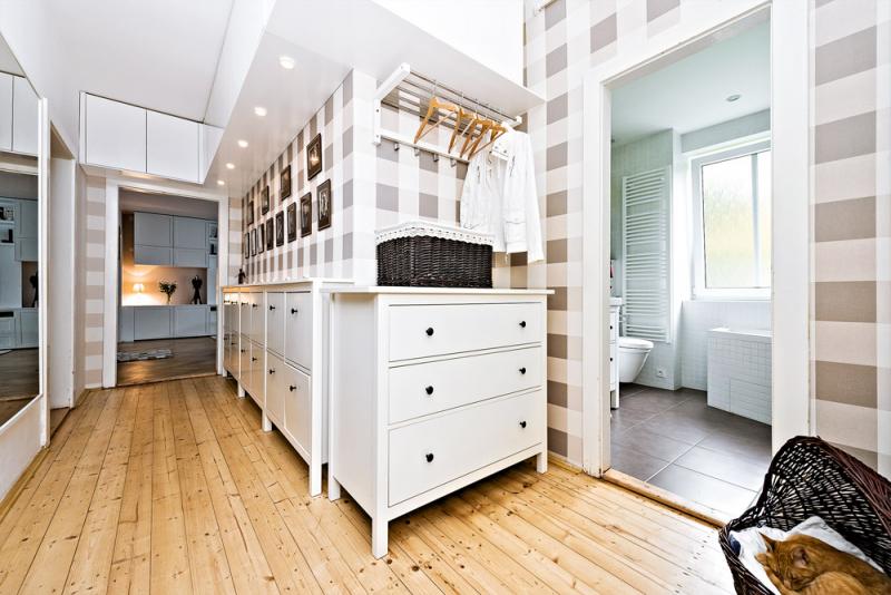 Také předsíň nabízí plno úložných prostorů, které ji ovšem díky bílé barvě nijak nezatěžují. O dekor se postarala kostkovaná tapeta, která si skvěle rozumí s přehozem v ložnici