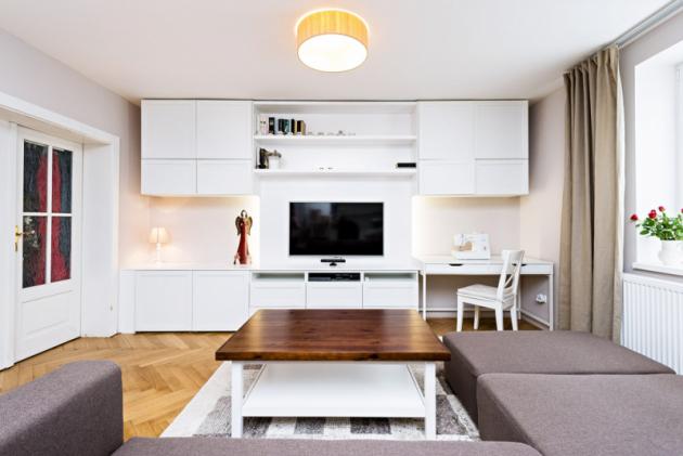 Efektně podsvícená deska s televizí ukrývá veškerou kabeláž a nábytková sestava s ní působí velmi čistě. Její nenápadnou a velmi praktickou součástí je i pracovní kout