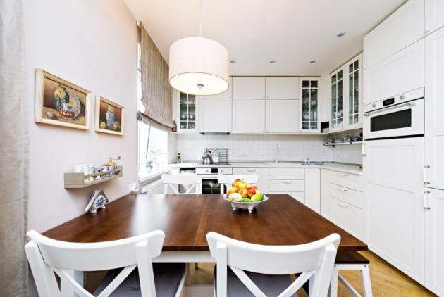Sytě hnědá deska kuchyňského stolu navazuje na desku konferenčního stolku a skvěle kontrastuje s bílou kuchyní v pozadí