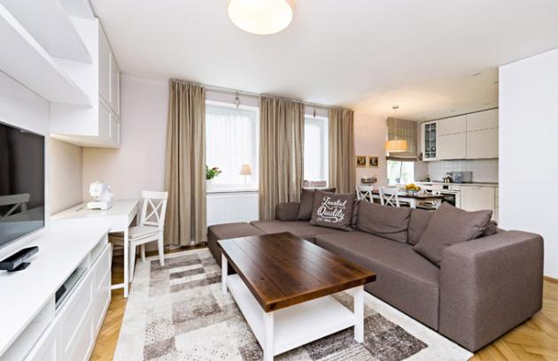 Obytný prostor s jídelnou a kuchyní designérka přirozeně propojila pomocí jednotného stylu, pečlivě sladěných barev a materiálů. dominantou pokoje je pohodlná sedačka od firmy Tom Tailor