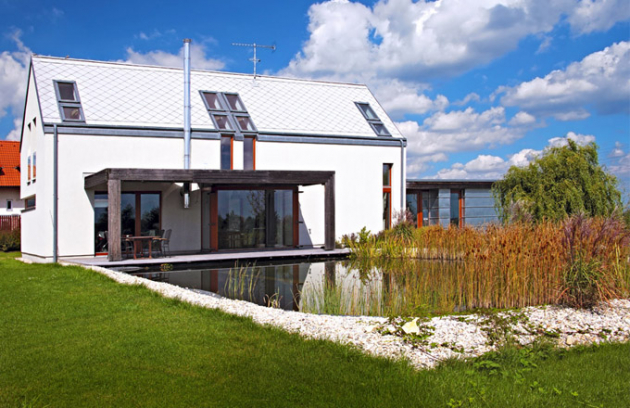 Moderní dům se sedlovou střechou je úzce provázaný francouzskými okny se zahradou. Rozlehlá terasa zastřešená pergolou orientovaná najih se zahezkých dní stává dalším obytným prostorem spřímou návazností nazahradu ajezírko