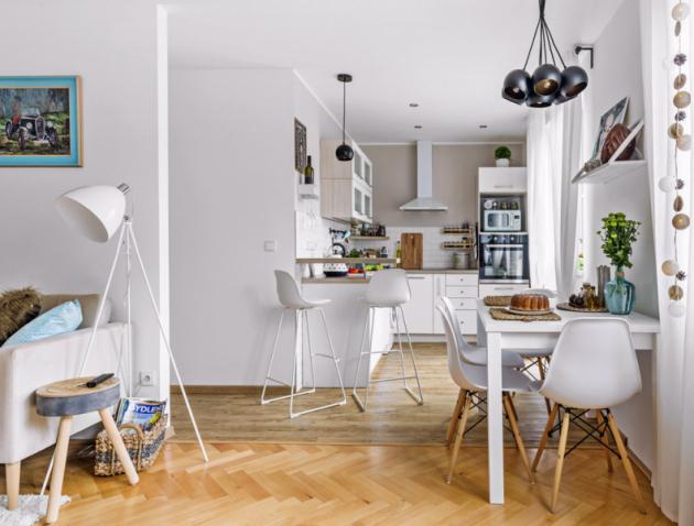Pojícím prvkem kuchyně aobývacího pokoje je jídelna sbílým stolem adesignovými židlemi. Zajímavým detailem jsou závěsná svítidla zakoupená vpražské prodejně Elusia