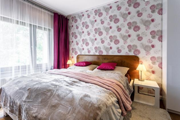 Čela jsou způvodní postele porodičích, rám postele, skříň anoční stolky jsou moderní vprovedení lesklý bílý lak, pořízené vIkea aXXXLutz. Zeď zapostelí zdobí květovaná tapeta zprodejny Tapety Metro Florenc