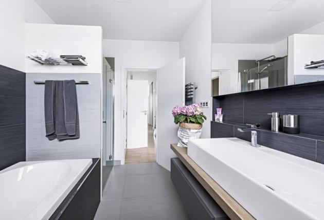 Minimalistická, barevně neutrální koupelna je nadčasová ajejí vzhled lze měnit libovolnými barevnými doplňky. Závěsné skříňky adeska zběleného povoskovaného dubu odpouzující vodu jsou vyrobené namíru