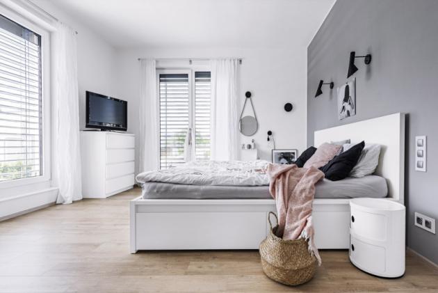 Sjednoduchým astrohým designem postele zIkea jsou majitelé spokojeni. Celkový dojem severského stylu dotvářejí noční stolky značky Kartell, svítidla Louis Poulsen, věšáky Dots odMenu…