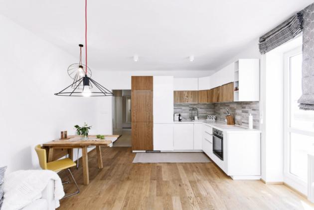 Odstín podlahy vhodně doplňuje barva jídelního stolu idvířek části kuchyňské linky. Drobné akcenty tak tvoří pouze barvy doplňků, které celou kompozici ozvláštňují, ale nenarušují