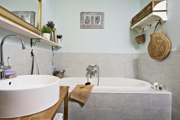 Koupelna je zařízena vpřírodních tónech adoplněna vtipnými detaily, třeba vpodobě zrcadla zarámovaného vestarém obrazovém rámu