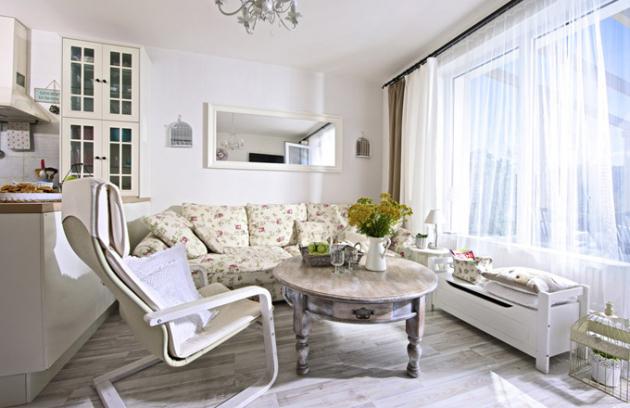 Dominantou obývacího pokoje je maximálně pohodlná obrovská pohovka skvětinovým vzorem koupená vKika. Doplňují ji subtilní bílé křeslo zIKEA azrenovovaný kulatý kávový stolek zbazaru