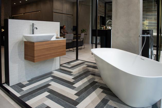 Snoubení tvarů  Dlažba stextilním vzorem vneobvyklé skladbě dominuje koupelně, v níž je umístěná samostatně stojící vana vyrobená zlitého mramoru. Tenkostěnná sanitární Saphir keramika od společnosti Laufen spolu s podumyvadlovou skříňkou, vyrobenou zhliníku a obloženou tenkou dřevěnou dýhou, dodává celé koupelně nezbytnou lehkost.