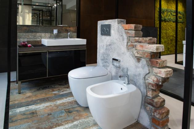 Syrový industriál  Design průmyslových továren evokuje koupelna, kde dekor dlažby připomíná oprýskaný lak na dřevěné podlaze, vkombinaci sostrými hranami plechovkových detailů se skleněným povrchem u podumyvadlové skříňky Geberit, působí velmi industriálně. Vše je zjemněno oblými tvary sanitárních zařizovacích předmětů, které vyvažuje ovládací tlačítko Geberit zpravé břidlice.