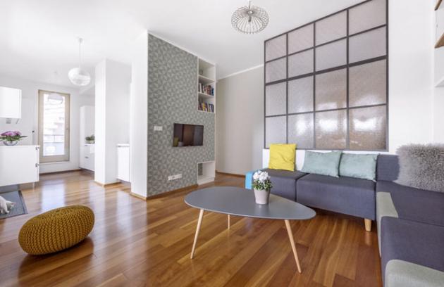 Kuchyň s obývacím pokojem propojuje jednolitý dřevěný dekor podlahy. Prostor zjemňují odstíny zelenkavé tapety a výmalba v nejsvětlejším barevném tónu tapety a stejně tak decentní barevné odstíny sedacího nábytku a konferenčního stolku