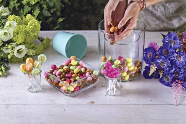 1. Dovětší vázy vložte nádobu menší – mezi stěnami by měl být volný prostor cca 1 cm. Mezeru mezi nádobami vyplňte bonbony tak, aby vnitřní nádoba nebyla vidět