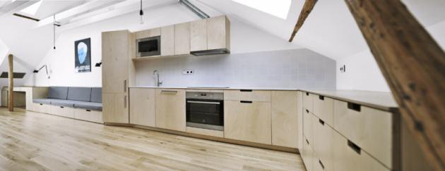 Nábytek je zhotovený zbřezové překližky, pracovní deska adřez jsou  zbílého akrylátu. Natočení chladničky o20 stupňů je praktické pro práci vkuchyni azároveň nápadněji odděluje kuchyň odobývacího prostoru, který se tak zdá být větší