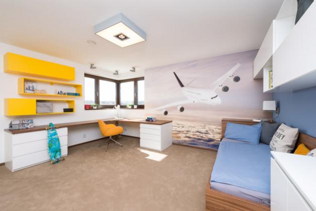 Dominantou chlapeckého pokoje je fototapeta sletadlem. Postel spolohovacím roštem poskytuje pohodlné azdravé spaní, rohový psací stůl nabízí prostor pro práci ipro hru. Předností pokoje je velký anezastavěný prostor