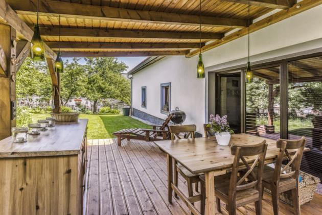 Terasa zastřešená dřevěnou pergolou je místem pro vychutnání kávy aprvním krokem dovelké přírodní zahrady