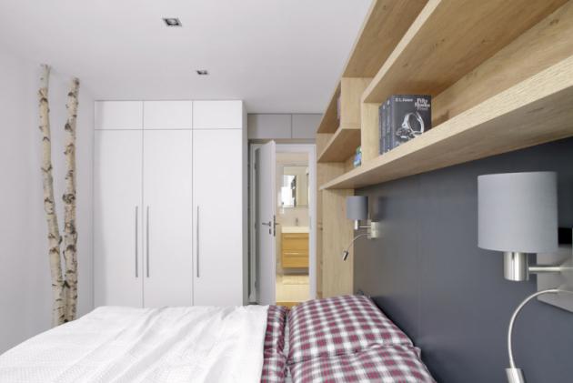 Načele postele jsou připevněné čtecí lampičky značky Eglo. Prostor pod postelemi je vyřešený formu úložných zásuvek, které se vysouvají doboku. Votevřených policích mají kočky své prolézačky. Našedé desce, tvořící čelo dvoulůžka jsou zavěšené noční stolky