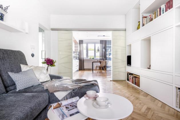 Probouráním zdi mezi dvěma místnostmi se krásně otevřel prostor mezi kuchyní aobývacím pokojem. Když je potřeba zavřít, zatáhnou se designové skleněné dveře svýplní Grafosklo