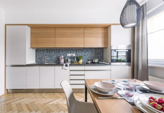 Použitím sádrokartonu nechala designérka kuchyň splynout se zdí. Levou pracovní aúložnou část doplňuje sestava skříněk smikrovlnnou troubou. Kuchyňskou sestavu ajídelní stůl vyráběl truhlář opět podle návrhu designérky