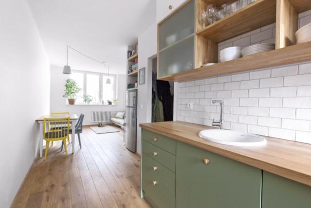 Horní část kuchyňské sestavy kombinuje otevřené police se skříňkami krytými sklem. Ustropu jsou skříňky zbílého lamina. Chladnička je umístěná vevyzděném výklenku