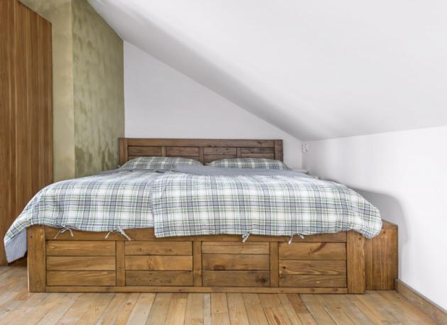 Postel zmasivního dřeva je vyrobená přesně namíru dovýklenku vpodkrovní šikmině