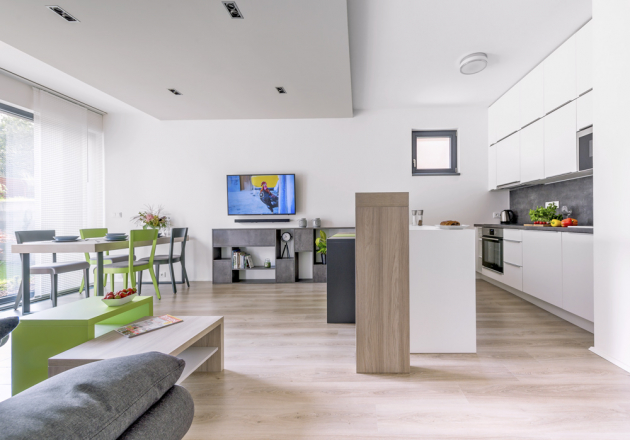 Přízemí domu tvoří velká místnost, která slouží jako kuchyň sbarovým posezením, jídelna aobývací pokoj