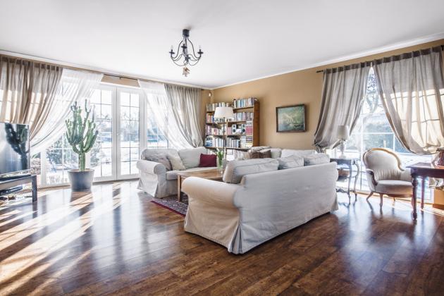 Díky množství rozměrných oken je obývací pokoj zalitý sluncem asamotný dům okna vizuálně odlehčují