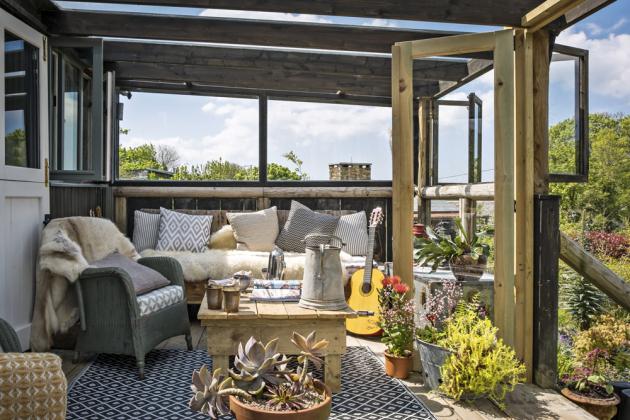 Přistavená veranda láká k posezení přes den i navečer. Originální ručně vyrobený nábytek i dekorace jsou laděné do přírodních tónů