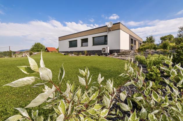 S betonovou stěrkou v obývacím pokoji zajímavě rezonuje skleněná posuvná příčka, která místnost dělí na dvě části zařízené s minimalistickým přístupem