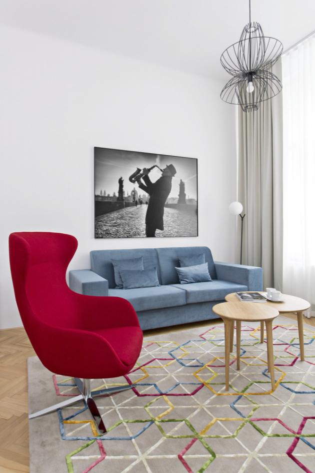 Rozkládací sedací souprava je odčeského výrobce Polstrin, černobílá fotografie saxofonisty naKarlově mostě je odJiřího Píši