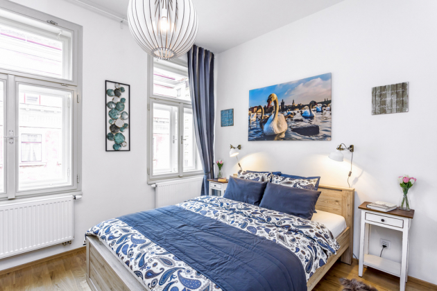 Dřevěný dekor postele astylové noční stolky alampičky dávají ložnici příjemný nádech. Závěsy zIkea ladil designér kbarvě obrazů