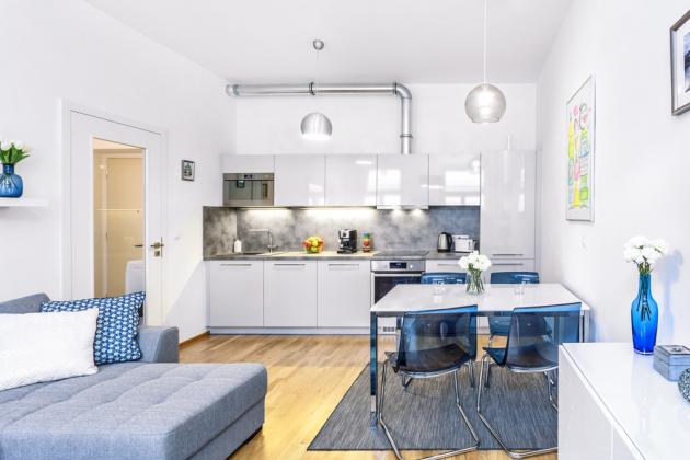 Kuchyňskou část tvoří sestava v odstínu silver grey odfirmy Hanák amoderní jídelní stůl splastovými židlemi nakovové konstrukci. Kuchyň situovaná dojedné linie nabízí dostatek úložného místa avestavěné spotřebiče, jako jsou kombinovaná chladnička, odsavač, trouba imyčka