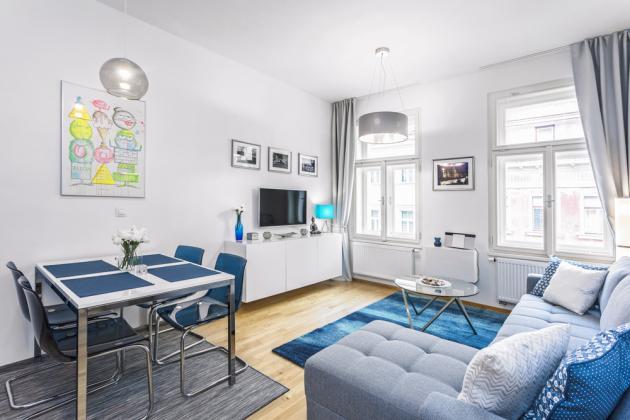 Vysoké stropy, velká okna aplocha 20,6 m2 se starají oto, aby obývací pokoj skuchyňským koutem ajídelnou nepůsobil stísněně