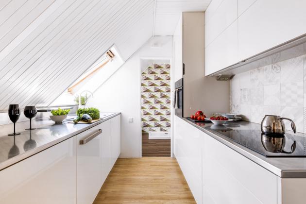 Praktickým, ale i hezkým prvkem je v kuchyni nerezová pracovní deska s prodlouženou hloubkou, která tak řeší střešní zkosení. V zahnutém profilu je skryté zabudované  LED osvětlení