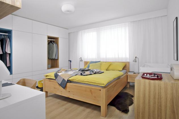 Postel měli majitelé objednanou už před tím, než se začal dělat návrh bytu. Je vyrobená nazakázku zmasivního dřeva, je vyvýšená avybavená úložným prostorem