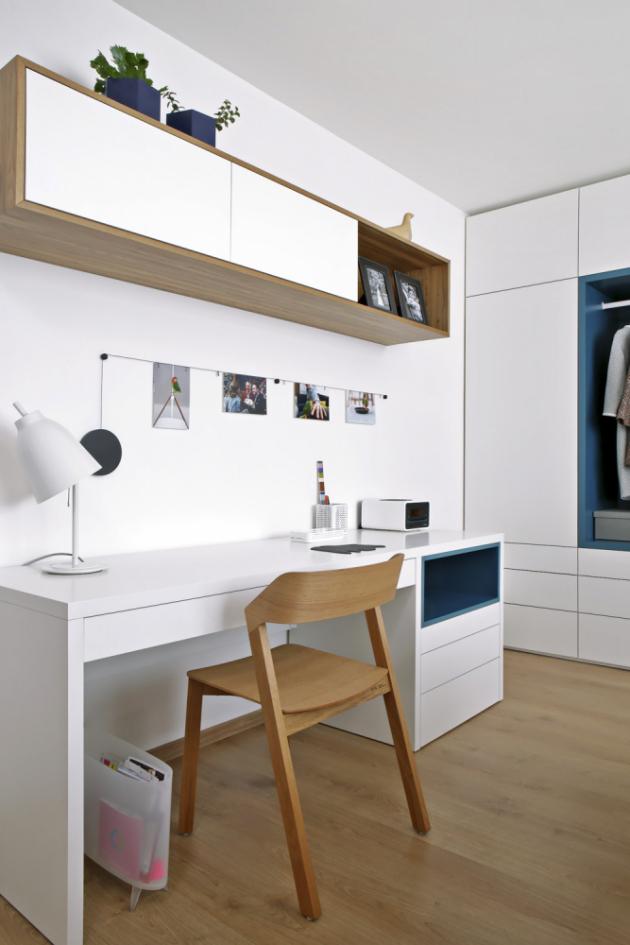 Barevné niky jsou zajímavým prvkem, který záměrně ruší celistvou plochu skříní. Vložnici se našlo místo také pro pracovní stůl