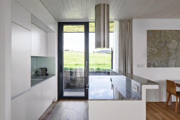 Osa domu tvoříprůhled odseveru kjihu. Je přepažovaná posuvnými dveřmi, které je možné zavřít, autvořit tak uzavřené jednotlivé prostory. Velká obytná místnost vpřízemí je propojená skuchyní ajídelnou