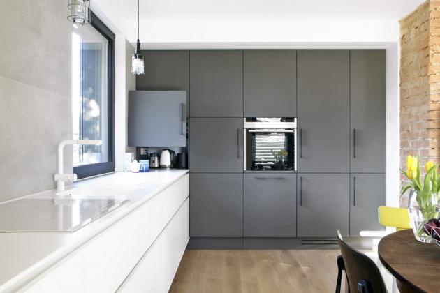 Kuchyň nazakázku dle návrhu architektky kombinuje bílá lakovaná dvířka ašedou stěnu skříní sdvířky Trachea, pracovní deska je zbílého corianu